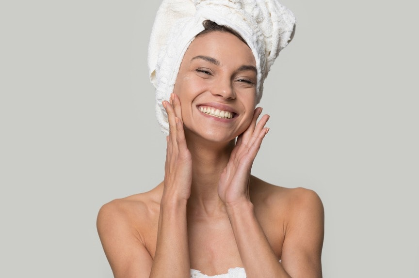 smiling-woman-with-towel-on-head-touch-clean-healthy-skin-picture-id1147400532 What Does Microdermabrasion Do For The Skin?